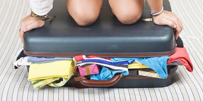 colocando roupas na mala de viagem